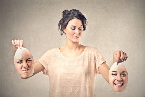 Mujer-sosteniendo-dos-caras-una-enfadada-y-otra-sonriendo